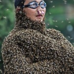 """Beekeeper Wang stands with bees partially covering his body on weighing scale during """"bee-attracting"""" competition in Shaoyang"""